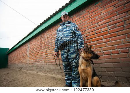 Omsk, Russia - August 22, 2014: Canine Center. German shepherd and policeman at the yard