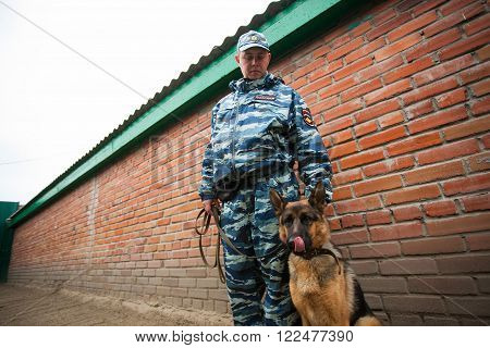 Omsk, Russia - August 22, 2014: Canine Center. German shepherd and policeman friendship