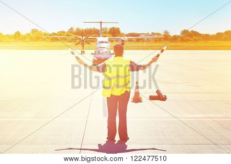 Plane on tarmac in the airport guided by ground staff. Taxiing