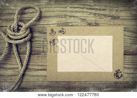 Frame with anchor and rope on wooden boards.