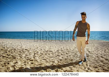 Full Length Shot of a Handsome Athletic Young Man in Trendy Attire, on a Beach in a Sunny Summer Day, Looking Away against Blue Sky Background.