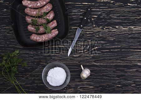 raw sausage in a frying pan with garlic, salt and knife on a wooden background, rustic