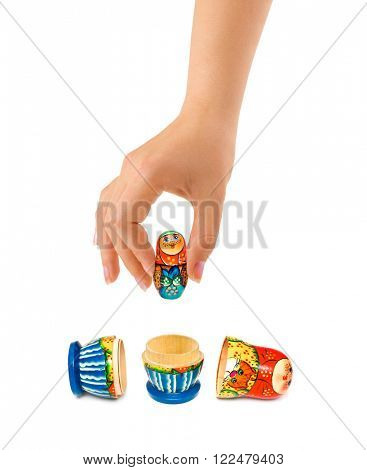 Hand and russian toy matrioshka isolated on white background