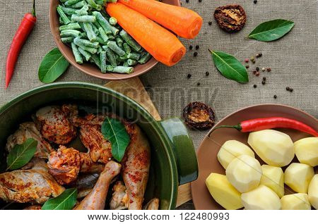 Top view of baked chicken with vegetables in round ceramic stew pot on linen fabric background