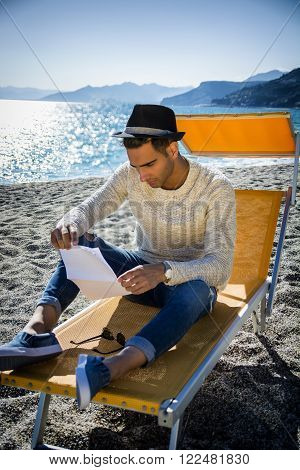 Young man on beach sitting on deckchair while reading letter. Seascape with hills on background