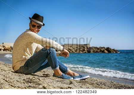 Full Length Shot of a Handsome Athletic Young Man in Trendy Attire, on a Beach in a Sunny Summer Day, Looking At Camera Smiling, against Blue Sky Background.
