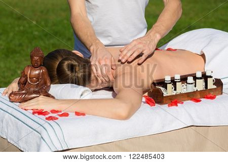 Professional rubber is doing massage to girl which laying on the sofa with oil and statuette of Buddha.