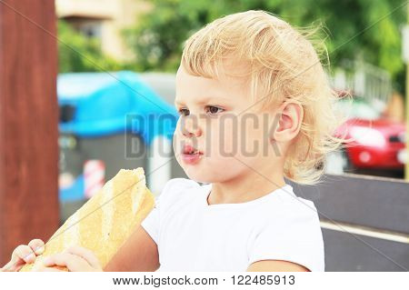 Blond Baby Girl Eating Big French Baguette