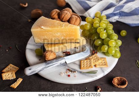 Cheese and snacks on a marble plate. Still life in a rustic style. Shallow DOF