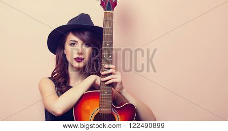 portrait of a beautiful young woman with brown guitar standing on the pink background