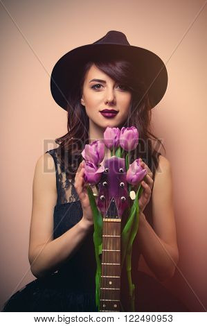 portrait of a beautiful young woman with purple tulips and brown guitar standing on the pink background