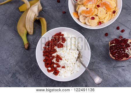 Healthy breakfast - corn flakes, goji berry, cottage cheese, milk and fruit. Top view
