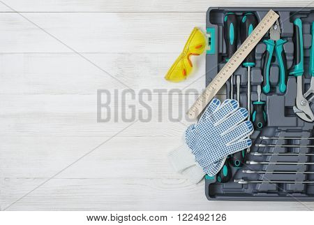 Open toolbox with different instruments on white wooden workbench with open space at center