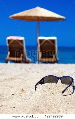 blue color of sea and glasses on sand. Focus on glasses