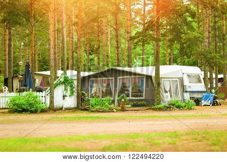 Summer outdoor recreation Scandinavian vacation. Camping vans and tents parked in a wooded campsite among pine trees. Finnish Gulf. Area for camp in woods. Hamina Finland Suomi