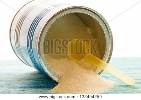 Powdered Milk, Baby Formula with spoon infant formula in can and bottle for feeding baby on blue wooden table. dairy food for baby  spilling out of a measuring scoop.