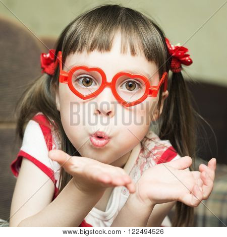 Cute little girl with glasses in the shape of a heart sends an air kiss