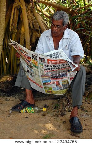 KALUTARA, SRI LANKA - DECEMBER 23, 2008: A middle-aged man reads a newspaper in the morning after the last night booze