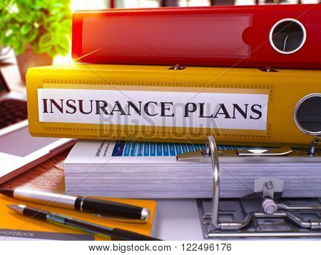 Yellow Office Folder with Inscription Insurance Plans on Office Desktop with Office Supplies and Modern Laptop. Insurance Plans Business Concept on Blurred Background. 3D Render.