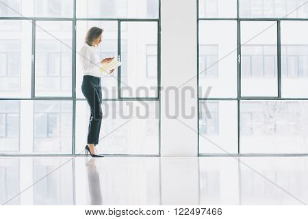 Photo business woman wearing modern suit, looking  mobile phone and holding papers in hands. Open space loft office. Panoramic windows background.