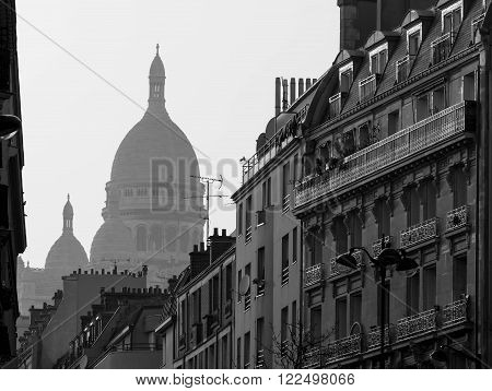 The black and white view of basilica Sacre Coeur and parisian street in the morning fog.