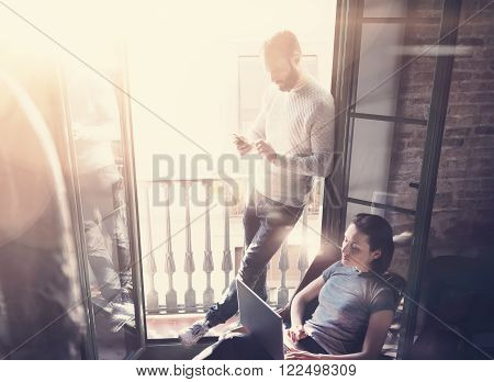 Young couple work together. Photo woman and bearded man working with new startup project in modern loft. Using contemporary notebook, smartphone.