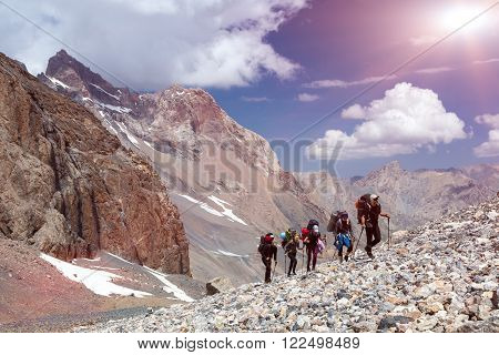 Five Members Team Sport Clothing Going Heavy Load Backpacks Climbing Gear Up  Mountain Peaks Blue Sky Majestic Summits Shining Sun Background