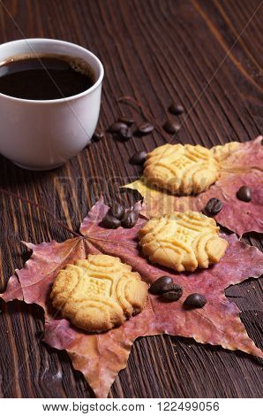 Cup of hot coffee and shortbread cookies on brown wooden table with autumn leaves