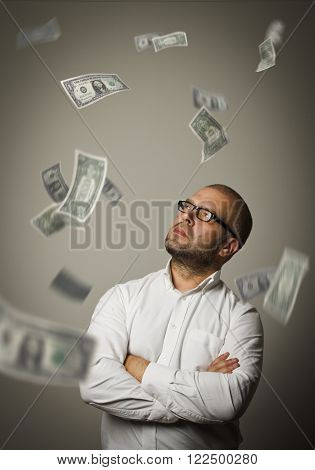 Man in white and falling dollar banknotes. Currency and lottery concept.