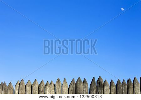 Palisade stockade pilings logs and blue sky. Abstract background, old, ancient.