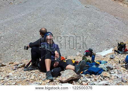 Female and Male Travelers lean on each other Totally Tired After Difficult Ascent Alpine Gear Dropped Around Backpacks Helmets Rocky Moraine on Background