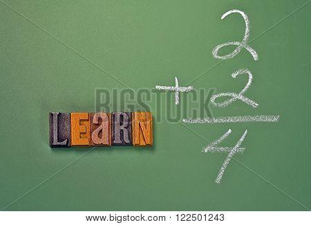 Word learn in vintage wooden letterpress type on green chalkboard.