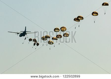 Military transport plane to a background of blue sky and a parachute jumpers