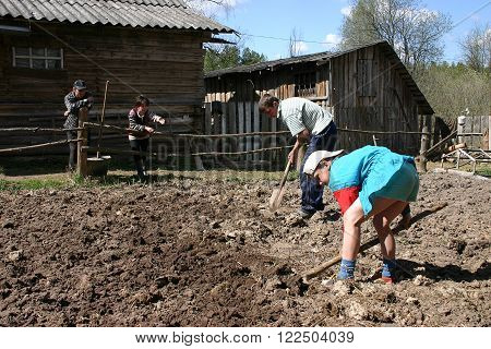 Tver, Russia - May 7 2006: The children a boy and a girl working in the field treated soil using shovels adult men and women watching the field work.