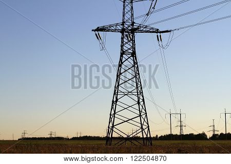 Electric tower. High-voltage transmission lines. Wires and tension. The higher the voltage. The tower at sunset. Industrialny landscape.