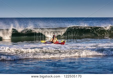 Kayaker facing the crest of a big wave in rough sea of Black Cove Nova Scotia coast Canada