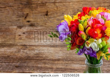 Fresh freesia flowers  on wooden table  background with copy space