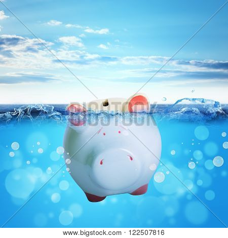 Piggy bank drowning in sea with blue sky