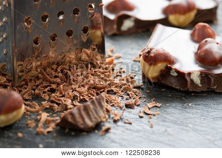 chocolate with nuts grated on a grater. close-up.