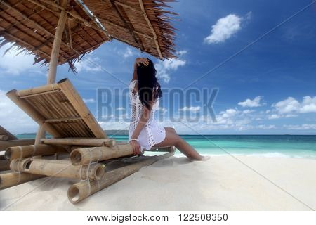 Woman sitting at chaise lounge with straw parasol on white sandy beach at Philippines