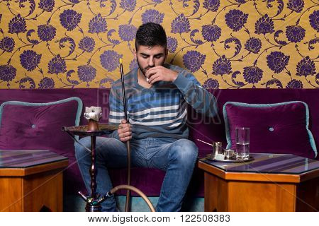 Man Smoking Shisha And Drinking Coffee