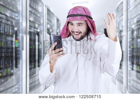 Arabic businessman looks happy while working with his mobile phone in the office