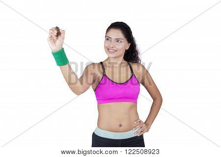 Picture of female athlete wearing sportswear and using marker to write something on copy space isolated on white background