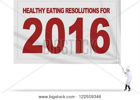 Picture of Asian female chef wearing uniform and drags a big flag of healthy eating resolutions for 2016