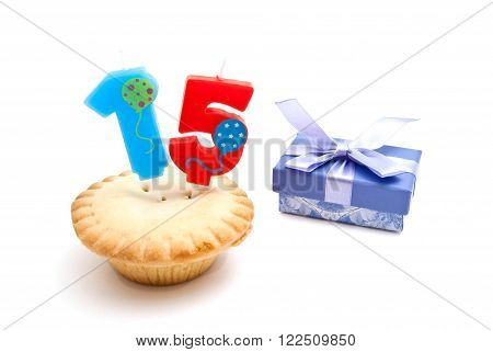 Cupcake With Fifteen Years Birthday Candle And Gift On White