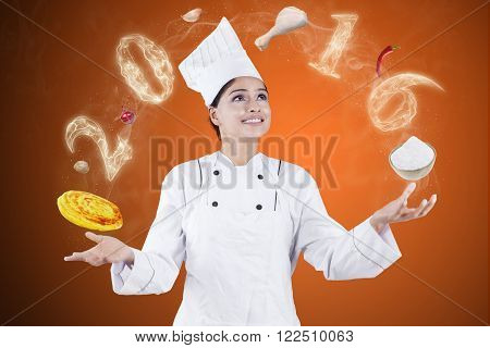 Portrait of female chef wearing a cooking wear juggling with meals and smoke shaped number 2016
