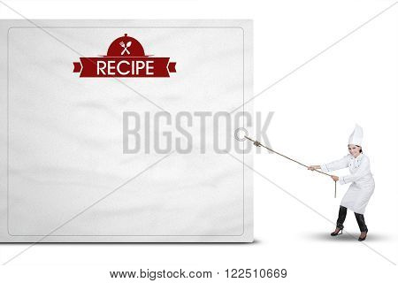 Picture of Indian woman wearing chef uniform and drags a billboard with recipe text isolated on white background