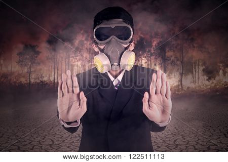 Young man wearing business suit and gas mask showing hands gesture to stop the fire forest
