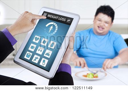 Overweight man eats a plate of salad in the kitchen with weight loss application on the tablet screen