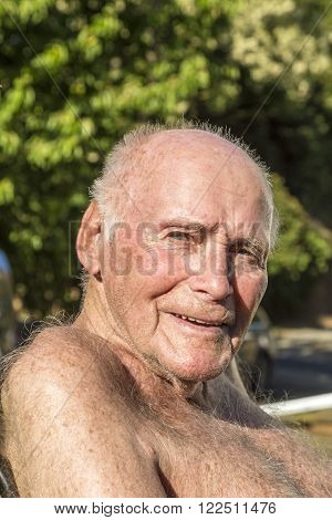 senior sits in the chair in the garden and enjoys the sun